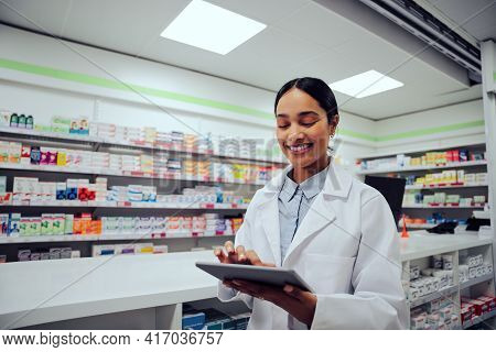 Portrait Of Smiling African Doctor Woman Working In Drugstore With Digital Tablet