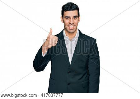 Handsome hispanic man wearing business clothes doing happy thumbs up gesture with hand. approving expression looking at the camera showing success.