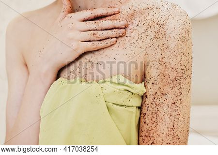 Woman Applying Body Exfoliating Scrub. Natural Organic Coffee Polish On A Woman's Hands And Breast.