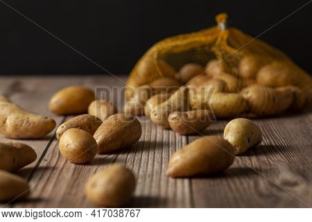 Shallow Depth Of Field Dark Image Of Small Irregular Shaped Ratte Potatoes Scattered On The Surface