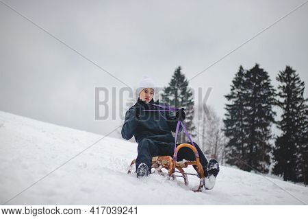 Teenager Caught Riding On A Wooden Sledge Trying To Adjust His Direction With His Hand And Concentra