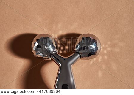 Cropped Shot Of Modern Metal Face Lift Roller Isolated Over Beige Background. Anti Age, Lifting And
