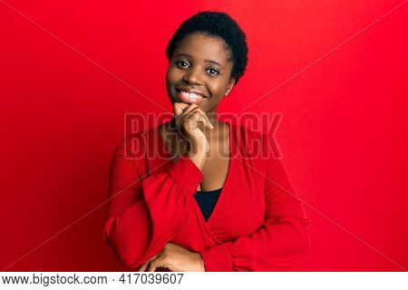 Young african woman with afro hair wearing casual clothes over red background smiling looking confident at the camera with crossed arms and hand on chin. thinking positive.