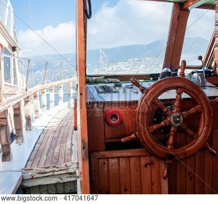 Yacht Steering Wheel And Control Panel. Ready To Sea Travel. Wooden Deck Interior Of Sailing Boat. S