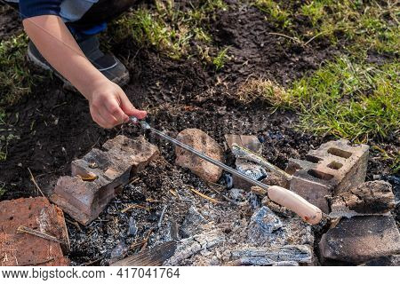 A Boy Fries A Sausage On A Skewer Over A Fire. Out Of Town Picnic Concept.