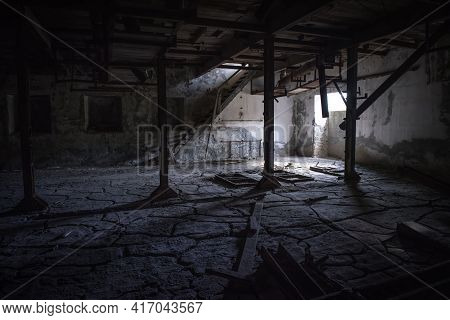 Abandoned Industrial Interior. Dark Room With Cracked Clay On The Floor, Broken Wooden Stairs And Ru