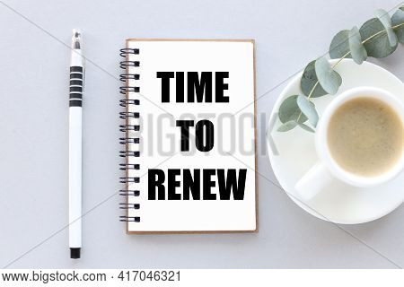 Time To Renew . Text On White Notepad Paper. Near Cups With Coffee And Plants On A Gray Background.