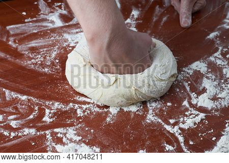 The Woman Kneads The Dough With Her Hands. Female Hands And Raw Dough On A Wooden Background. Pizza