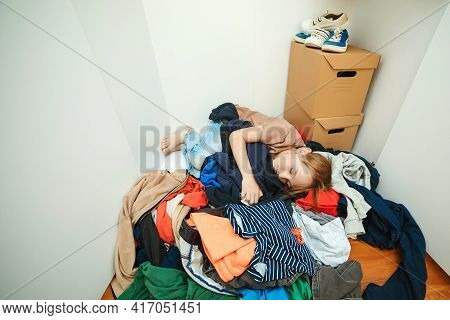 Lazy Boy Sleeping On The Pile Of Thrown Clothes. Mess In Open Wardrobe. Untidy Clutter Clothing Clos