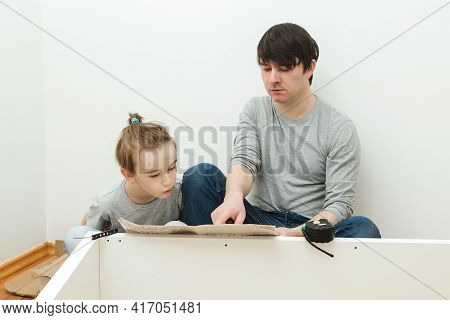 Father And Child Reading Instruction For Furniture Assembly. Dad And Little Son Assembling Furniture