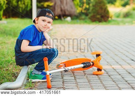Boy Falling Off His Scooter. Kid Getting Hurt While Riding A Kick Scooter. Unpset Child On A Walk. B