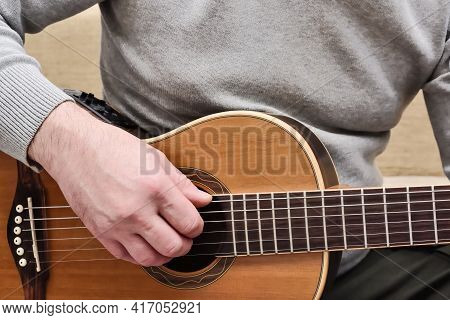 Man Playing On Acoustic Guitar. Close Up View Of Guitarist Hands And Guitar Body While Practicing An