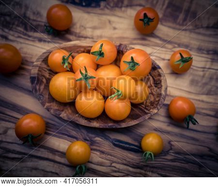 Orange Cocktail Tomatoes Solanum Lycopersicum On Olive Wood