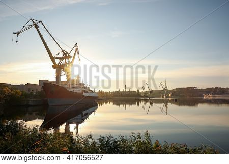 Big Cranes And Vessel At Shipyard On Sunny Day