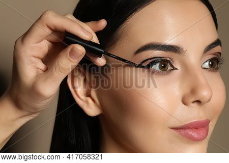 Artist Applying Black Eyeliner Onto Woman's Face On Beige Background, Closeup