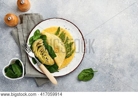 Omelette Or Omelet Stuffed With Asparagus, Avocado And Spinach Leaves For Breakfast On White Plate O