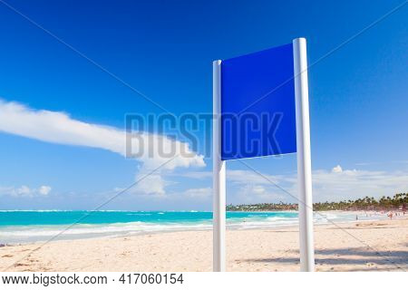 Blank Blue Billboard Stands On An Empty Tropical Beach On A Sunny Day. Background Photo Mockup Templ