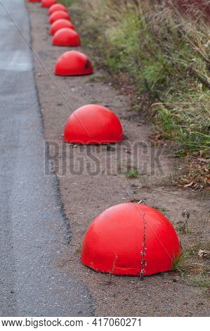 Red Concrete Anti-parking Hemisphere-shaped Bollards Stand In A Row Along A Roadside