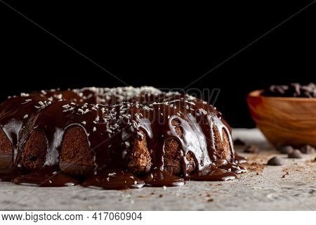 Side View Of A Round Chocolate Cake With Melted  Pudding Icing And Chocolate Chips In A Bowl In The