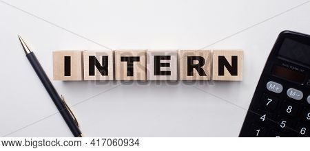 On A Light Background Between The Calculator And The Pen There Are Wooden Cubes With The Word Intern
