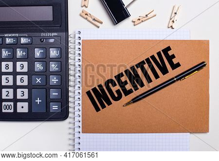 On The Desktop Is A Calculator, A Pen And Clothespins Near A Notebook With The Text Incentive. Busin