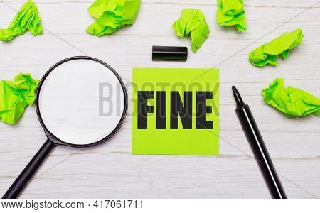 The Word Fine Written On A Green Sticky Note Next To A Magnifying Glass And A Black Marker On A Wood
