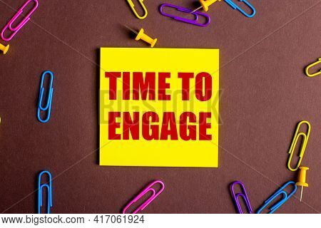 The Words Time To Engage Is Written In Red On A Yellow Sticker On A Brown Background Next To Multi-c