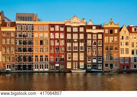 Hhouses and tourist boats on Amsterdam canal pier Damrak on sunset