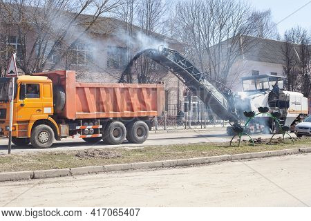 A Special Milling Machine Removes The Asphalt From The Road. A Crumb Of The Asphalt Is Poured Into T
