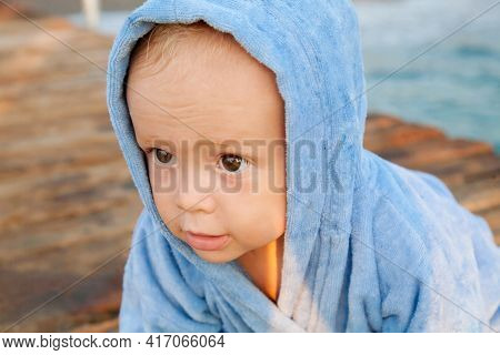 Сute Baby Boy Resting On The Beach Wrapped In A Towel Robe After Swimming. Summer Beach Vacation Con