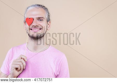 Cute Smiling Boy Is Holding Red Decorative Sign Of Heart. Young Man Cupid In Pink T-shirt Is Express