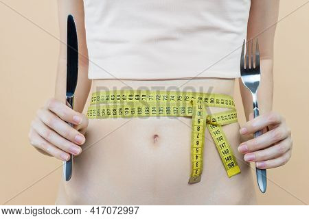 Closeup Of Female Slender Tummy Tied With Centimeter Tape. Young Woman Is Holding Fork, Knife. Diet