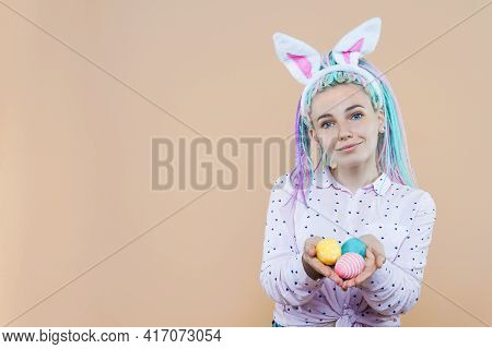 Pretty Girl In Bunny Ears, Pink Shirt Is Holding Eggs. Young Woman With Colored Dreadlocks Is Prepar