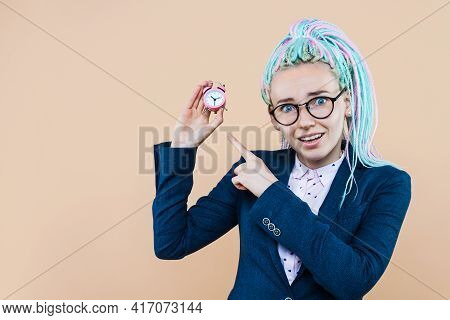 Successful Business Lady Is Smiling, Holding Pink Alarm Clock. Young Woman With Colored Dreadlocks,