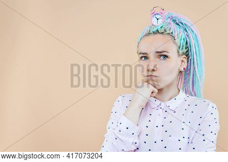 Thoughtful Cute Girl Freelancer Is Holding Pink Alarm Clock. Young Woman With Colored Dreadlocks Is