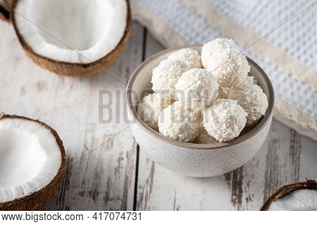 Portions Of White Chocolate Coconut Candy Balls In The Bowl, Raw Cracked Coconut On The Background