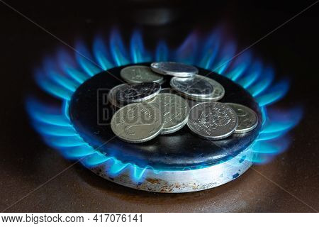 The Concept Of Increasing The Price Of Natural Gas For Russians. Coins Lying On A Burning Gas Stove.