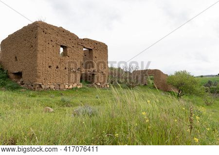 Abandoned And Deserted Clay House At The Top Of A Hill Against Stormy Cloudy Sky.