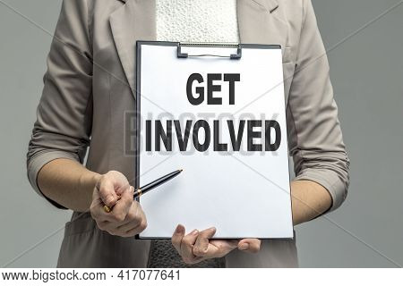 Pretty Woman Showing Card With Get Involved Against Grey Background. Business Or Education Concept.