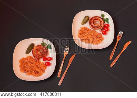 White Plates With Roasted Sausage And Stewed Cabbage On Dark Background. Top View.