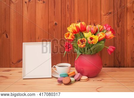 Colorful Tulips In Pink Vase, Cup Of Coffee With Macaroons And White Frame On Wooden Table. View Wit