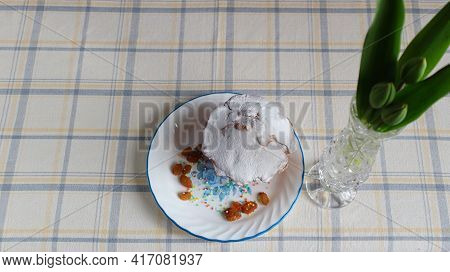 A Sweet, Delicious Raisin Muffin Sprinkled With Powdered Sugar On A White Plate With A Blue Border A