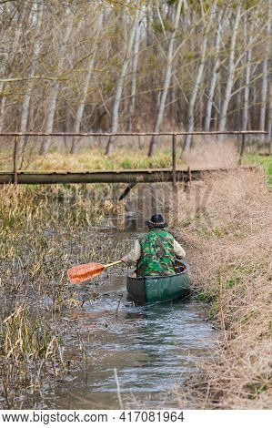 The Paddler Floats On A Canoe Along A Small Overgrown River.
