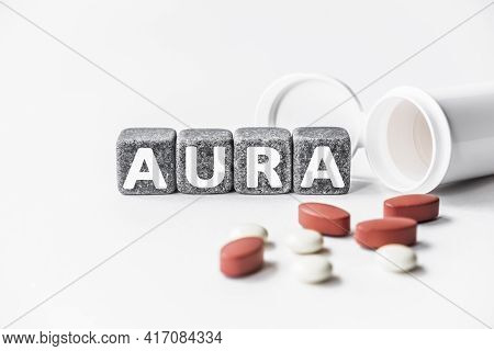 Word Aura Is Made Of Stone Cubes On A White Background With Pills. Medical Concept Of Treatment, Pre