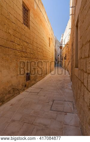 Ancient Narrow Street In Mdina, Malta. Old Buildings With Old Fashioned Lanterns.