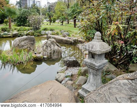 Traditional Asian Lantern Near Pond In Garden Of Russian-japanese Friendship. Urban Landscaping In S