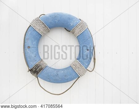 Blue Lifebuoy With Rope On White Wooden Background. Symbol Of Travel And Vacation. Rescue Device.