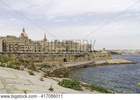 Panorama Of Valletta, Capital Of Malta. Ancient Buildings With Old Fashioned Balconies And Urban Roa