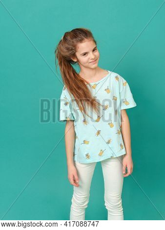 10 Year Old Girl In A Blue Shirt And White Jeans On A Green Background