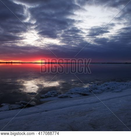 Evening Sunset Over A River Clear Of Ice And A Snow-covered Shore, Ice Drift In Spring. Spring Is Co